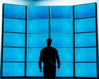 Homme devant des écrans